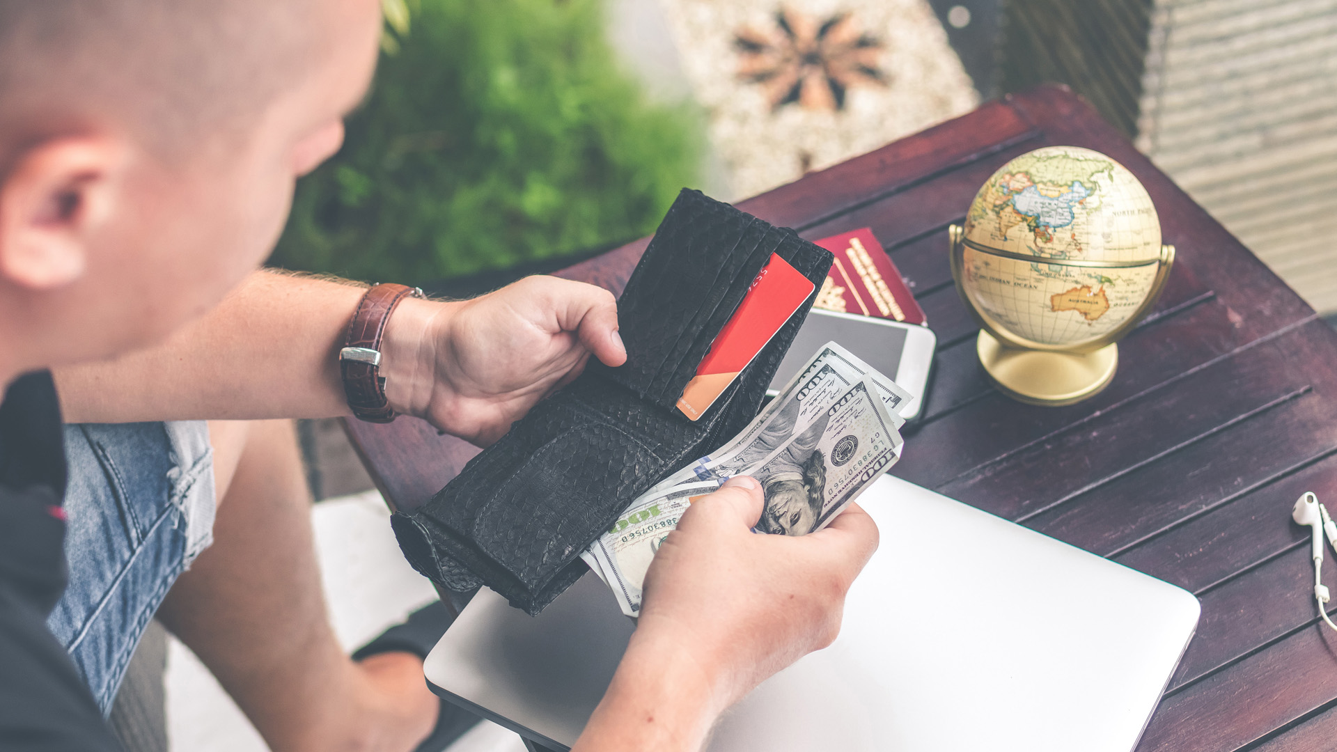 Man Checking Money In Case Of Holiday Fraud
