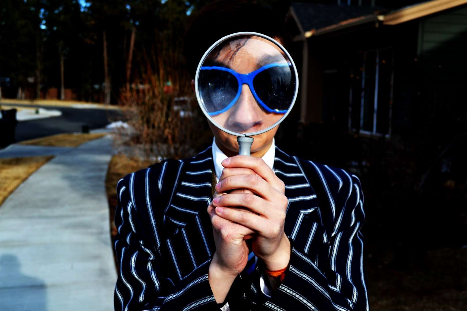 Man In Suit and Sunglasses Looking Through a Magnifying Glass